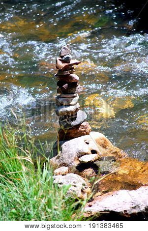 Zen stones displayed in a lake ravine outdoors.