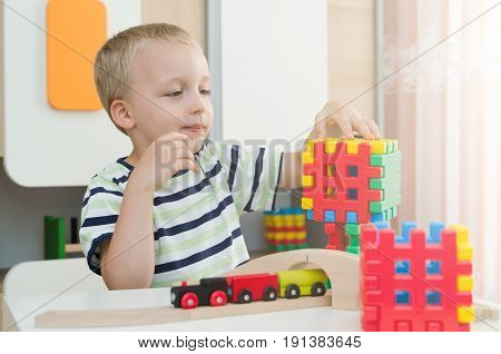 Little Boy Playing With Blocks On A Table