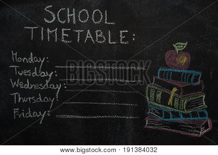 School timetable and stack of books with apple drawn with chalk on blackboard. Education, school concept