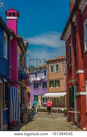 BURANO, ITALY - MAY 23, 2017: Tourist walking in the colorful alley of Burano island