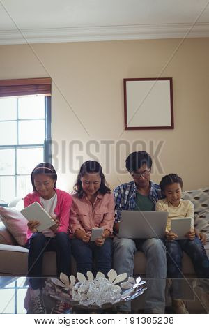 Family using laptop, digital tablet and mobile phone in living room at home