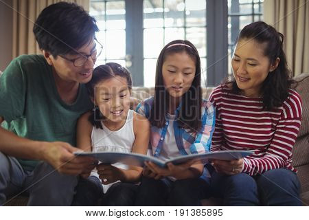 Family watching photo album together in living room at home