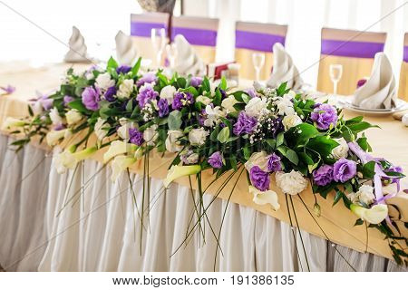 Flower arrangement on the table. Purple and white flowers. The concept of a party and wedding decor.