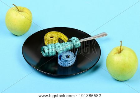 Apples And Black Ceramic Plate With Measuring Tapes