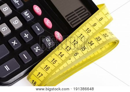 Calculator in black colour with 100 figure and yellow tape for measuring folded next to it isolated on white background. Concept of size measurement
