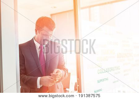 Mature businessman buttoning sleeve in office