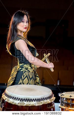 beautiful asian long haired drummer girl with drumsticks, studio shot on a dark background.
