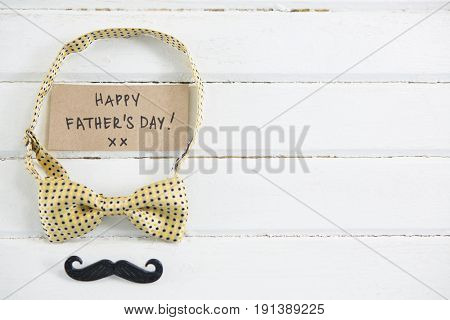 Close up of happy fathers day text with bow tie and mustache on white table