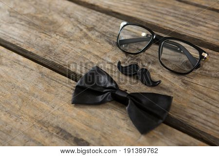 High angle view of bow tie with mustache and eyeglasses on wooden table