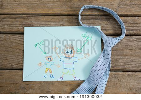 Overhead view of fathers day greeting card with necktie on wooden table