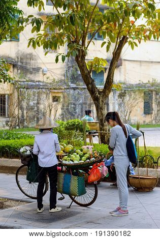 Street vendor transporting and selling goods in the streets of Hanoi Vietnam