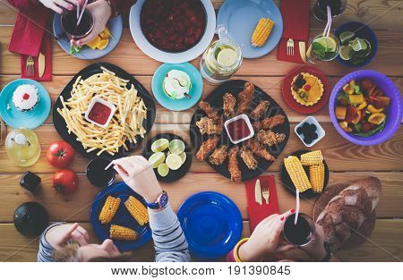 People with drinks while sitting at the dining table. Food on the table. Food on the table. People eat fast food.