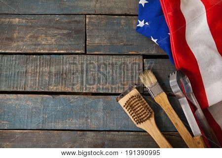 Basting brush and tong with American flag arranged on wooden table
