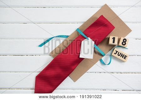 Overhead view of necktie gift by calender on white table