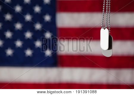 Close-up of dog tag hanging against American flag background