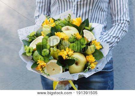Green and yellow bouquet of flowers and edible fruits and vegetables