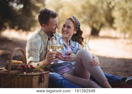 Smiling young man and woman looking at each other while holding wineglasses at farm