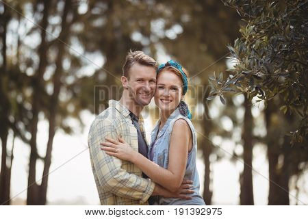 Portrait of smiling young couple embracing by olive tree at farm