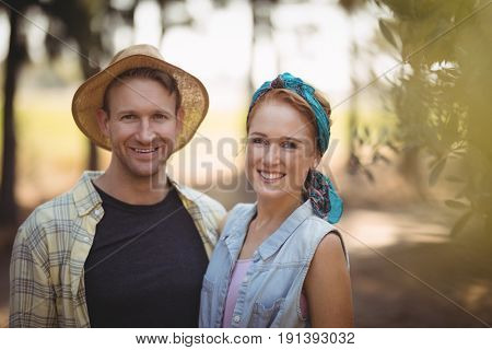 Portrait of happy young couple standing by trees at farm