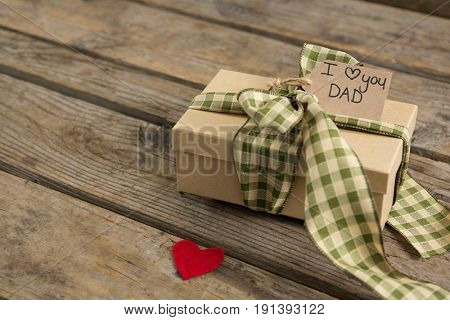 High angle view of text on tied gift box at wooden table