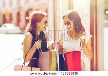 sale, consumerism and people concept - happy young women with shopping bags talking at shop window in city