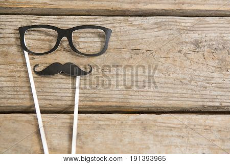 Overhead view of eyeglasses and mustache on wooden table
