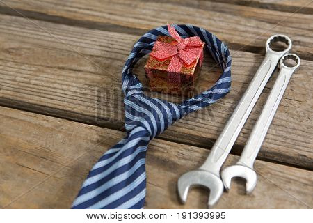 High angle view of gift box with necktie and work tools on wooden table