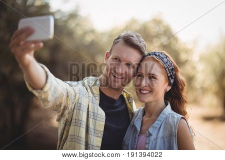 Cheerful young couple taking selfie at olive farm on sunny day