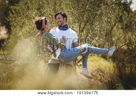 Smiling young man carrying girlfriend by trees at farm