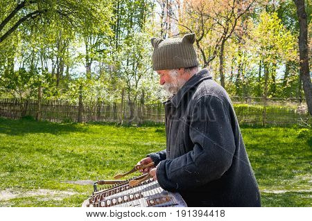 Kyiv Ukraine - April 23 2017: An elderly Ukrainian man a peasant with a long mustache and beard plays an ancient musical instrument of cymbals. Spring landscape. Old Street Musician. Museum Pyrohiv
