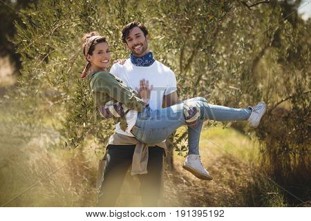 Portrait of smiling young man carrying girlfriend by trees at farm
