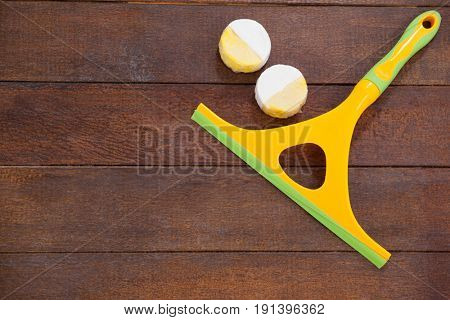 Squeegee and soap on a wooden floor