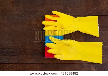 Overhead view of yellow gloves with scouring pad on a wooden floor