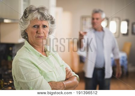 Portrait of unsmiling senior woman with angry man in background at home