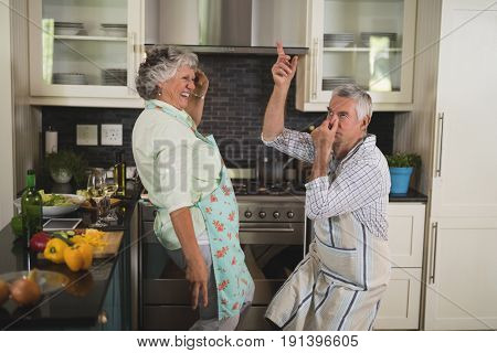 Playful senior couple spending leisure time in kitchen at home