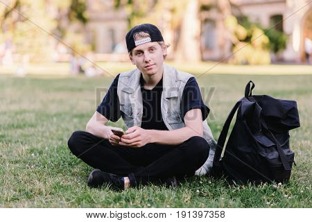 A student sitting on the grass at the university campus park and using a mobile phone on the background of a college campus. Student Life.