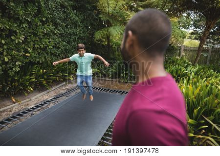 Side view of father looking at son jumping on trampoline
