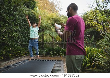 Rear view of father photographing son while jumping on trampoline at park