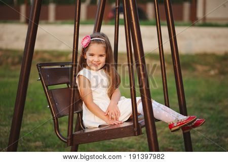 photo of young happy girl on the swings