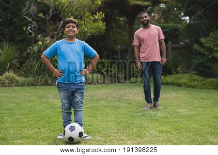 Portrait of smiling boy standing by soccer ball with father in background at park