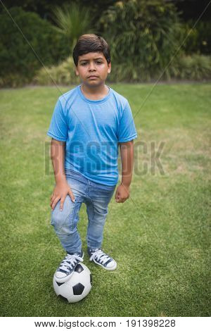 Portrait of upset boy standing with soccer ball on field at park