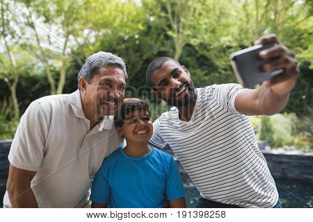 Happy multi-generation family taking selfie together at park