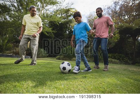 Smiling multi-generation family playing with soccer ball together on field at park