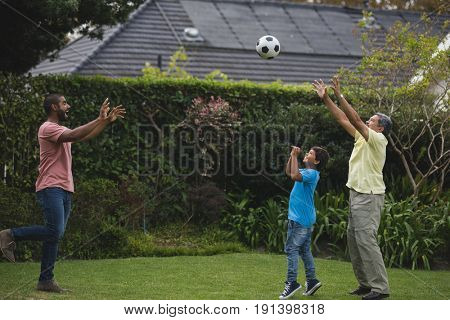 Happy multi-generation family playing with soccer ball together at park