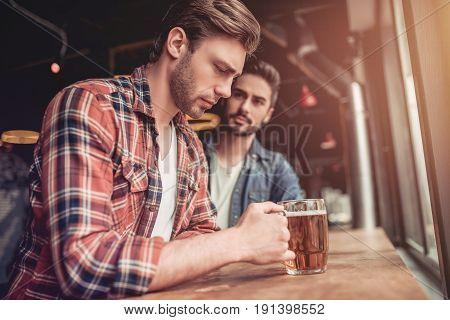 Upset man in bar. Friend's support. Beer mugs