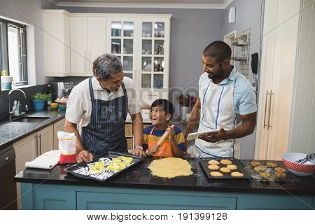 Happy multi-generation family preparing food together in kitchen at home