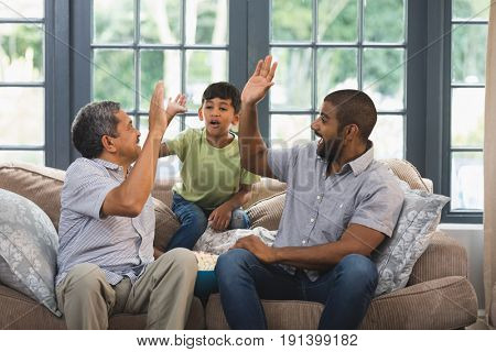 Multi-generation family giving high five while sitting together on couch at home