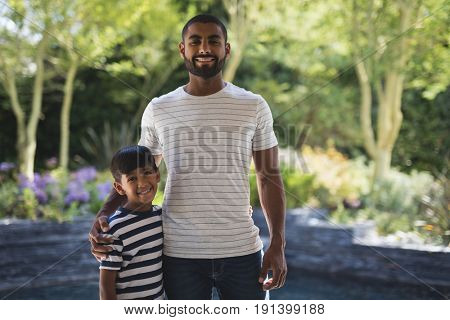 Portrait of smiling young man with his son standing at porch