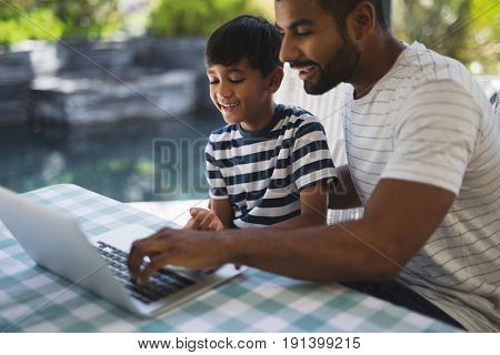 Happy young man with his son using laptop on table at porch