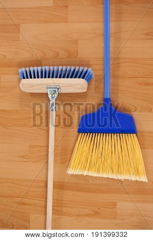 Close-up of two sweeping brooms on wooden floor